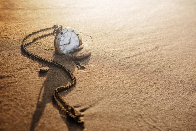 Винтажные карманные часы на золотом песчаном пляже Premium Фотографии