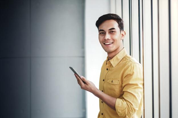 オフィスの窓のそばに立って幸せなビジネスマンの肖像画。スマートフォンを使用して笑顔。カメラを見て Premium写真