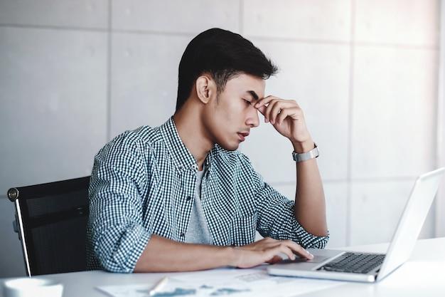 コンピューターがオフィスの机の上に座って疲れやストレス青年実業家 Premium写真