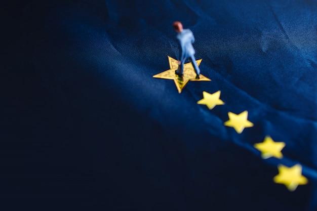 ビジネスまたは才能の概念の成功。黄色の黄金の星の上に立っているミニチュア実業家のトップビュー Premium写真