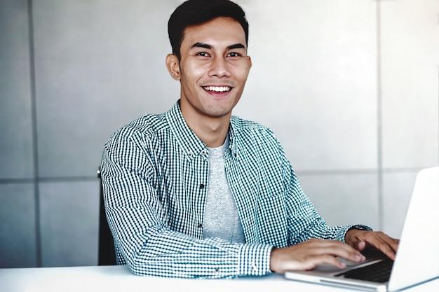 オフィスでコンピューターのラップトップに取り組んでいるスマートな若いアジア系のビジネスマン Premium写真