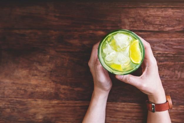 女性飲むアイスレモネードコンセプト。グラスのカイピリーニャまたはトロピカルレモンジュースでリラックス Premium写真