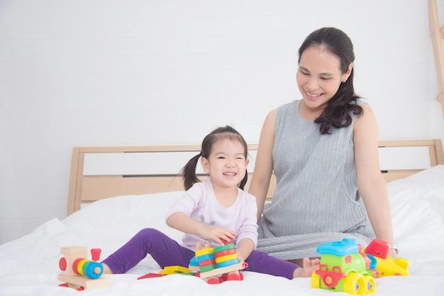 彼女の母親と一緒におもちゃをするリトルアジアンガール Premium写真