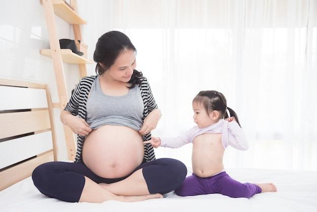 美しいアジアの妊娠と彼女の娘はベッドの上に腹を見せている Premium写真