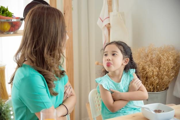 小さなアジアの女の子は彼女の母親と一緒に朝食をとることを拒否 Premium写真