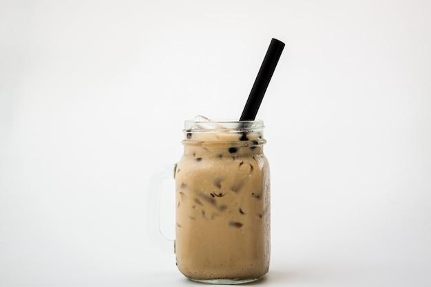 アイスミルクティーとボバ泡冷たい飲み物を白い背景の上のガラス Premium写真