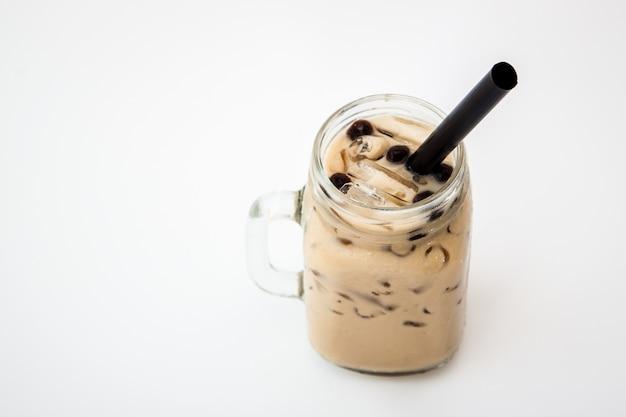 アイスミルクティーとボバの泡の白い背景の上の冷たい飲み物のガラス、アイスミルクティーとボバの泡の分離 Premium写真