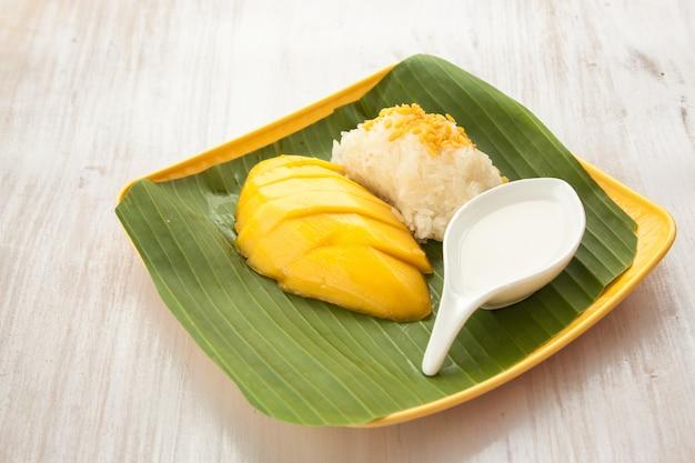 バナナの葉と黄色プレートタイのデザートにマンゴーとライスをスティックします。 Premium写真