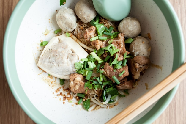 Закройте сушеную лапшу со свининой тофу, фрикадельками и вареной свининой в большой миске на фоне дерева Premium Фотографии