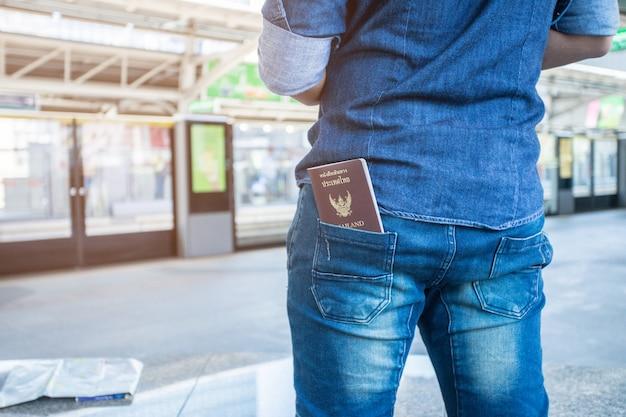 Путешественник и тайский паспорт в джинсовых шортах багажа Premium Фотографии