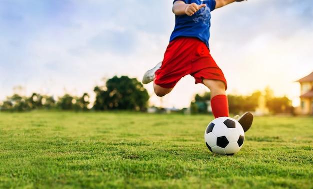 Активная спортивная картина ребенка, играющего в футбол, для упражнений в сообществе под Premium Фотографии