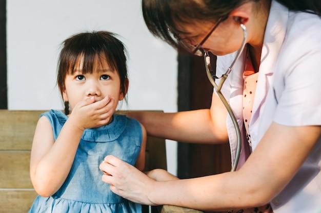 Врач с помощью стетоскопа, проверка дыхания ребенка. концепция болезни и здоровья. Premium Фотографии