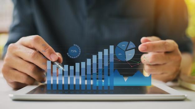 デジタル拡張現実感のグラフィックと会社の財務報告のバランスを分析する実業家。 Premium写真