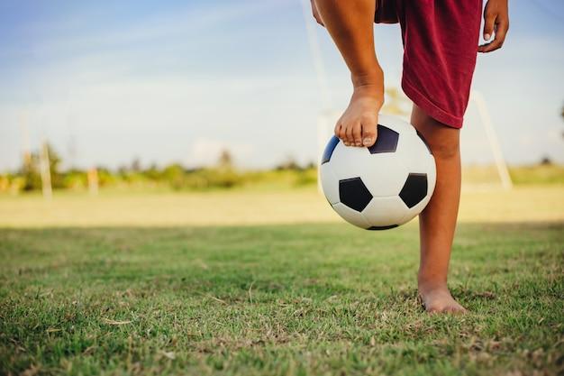 サッカーをして楽しんでいる子供たちのグループの屋外アクションスポーツ Premium写真