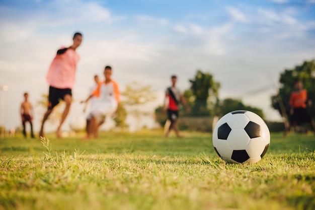 Активный отдых на свежем воздухе группы детей, играющих в футбол Premium Фотографии