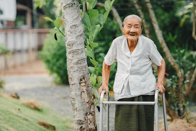 Бабушка гуляет с уокером в саду Premium Фотографии
