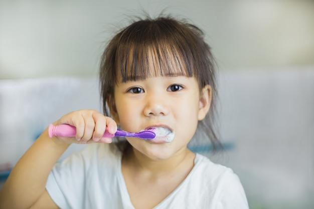 Маленькие дети используют зубную щетку для чистки зубов Premium Фотографии