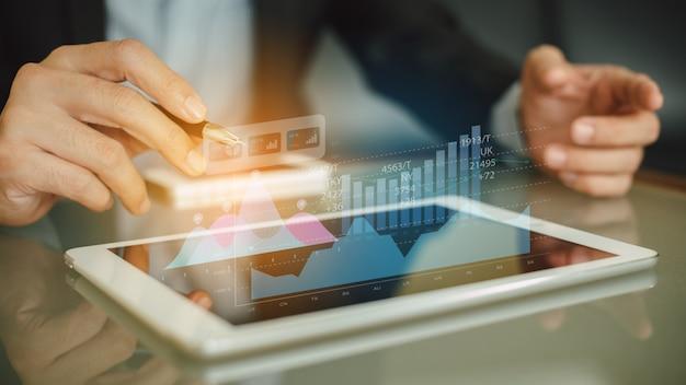 Бизнесмен анализируя данные взаимного фонда компании финансовые с цифровой технологией графики дополненной реальности. Premium Фотографии