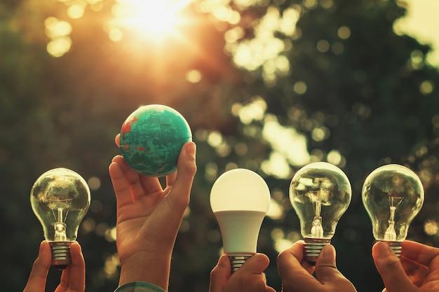 日没の電球と世界のおもちゃを保持して手。自然エネルギー Premium写真