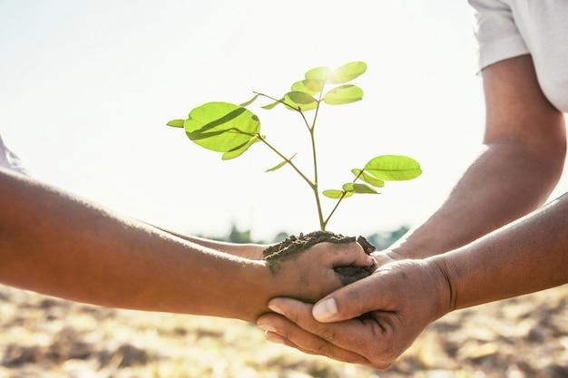 母親と子供たちが若い木を植えるのを助けます。コンセプトグリーンワールド Premium写真