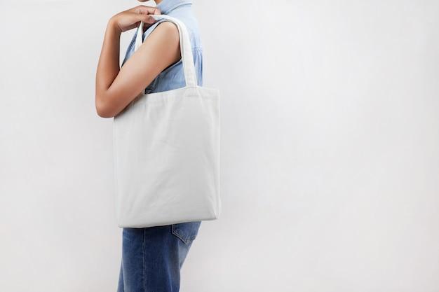 Женщина, держащая эко ткань изолят на сером фоне Premium Фотографии