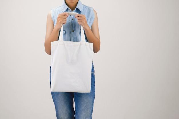 エコ布バッグを保持している女性を灰色の背景に分離します。 Premium写真