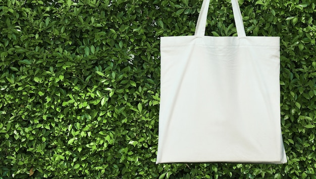 緑の葉の背景に空白の白いコットンバッグ。エコフレンドリーなコンセプト Premium写真