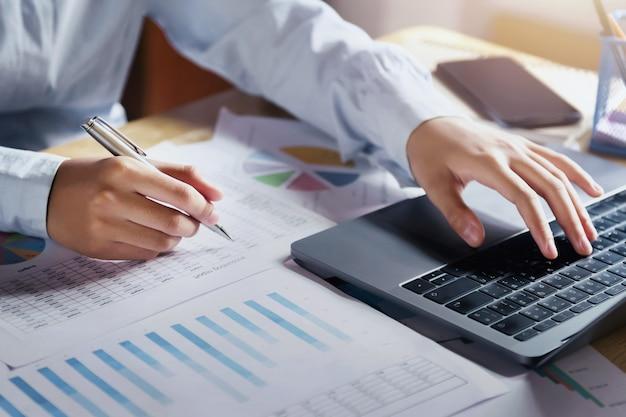 実業家のオフィスで財務のチェックデータのラップトップを使用して机の上の作業 Premium写真