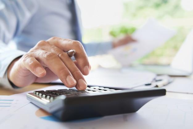 計算データファイナンスと会計のためのオフィスで働くビジネスマン Premium写真