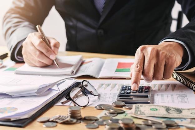 Бизнесмен работает в офисе, используя калькулятор для расчета бюджетных денег Premium Фотографии