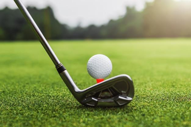 クローズアップゴルフクラブとゴルフボールの夕日と緑の芝生 Premium写真