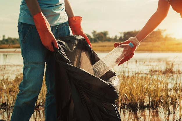 川での清掃のためのゴミプラスチックを拾う女性の手 Premium写真