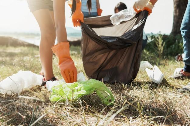 Женщина-волонтер собирает мусор для очистки в речном парке Premium Фотографии