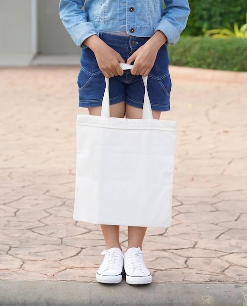 Молодая модель держит белую сумку для макета пустой шаблон Premium Фотографии