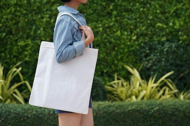 Молодая женщина, держащая белая сумка из ткани в парке Premium Фотографии