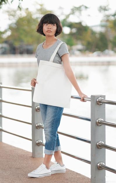 Битник женщина с белой сумкой в парке Premium Фотографии