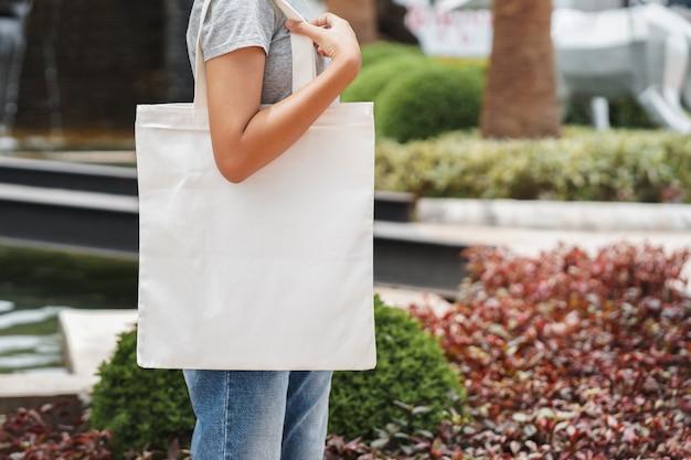Битник женщина с белой хлопчатобумажной сумкой в парке Premium Фотографии