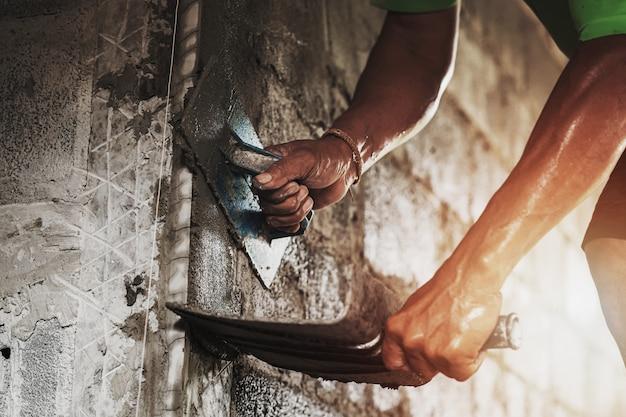 家を建てるための壁にセメントを左官労働者のクローズアップ手 Premium写真