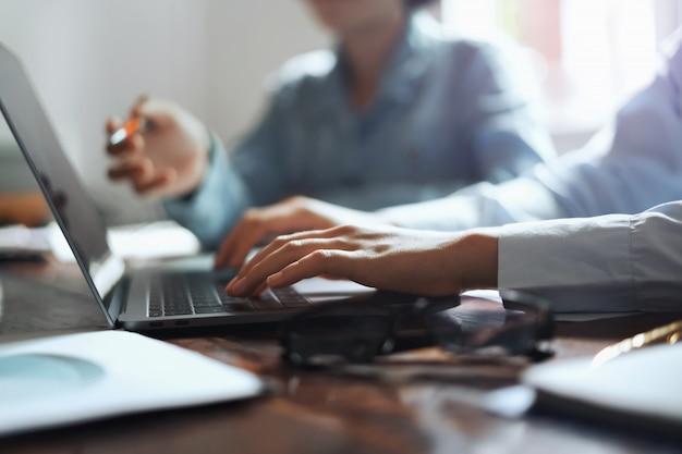 オフィスの会議チームのキーボードで入力するラップトップの手を使用してビジネスの女性。 Premium写真