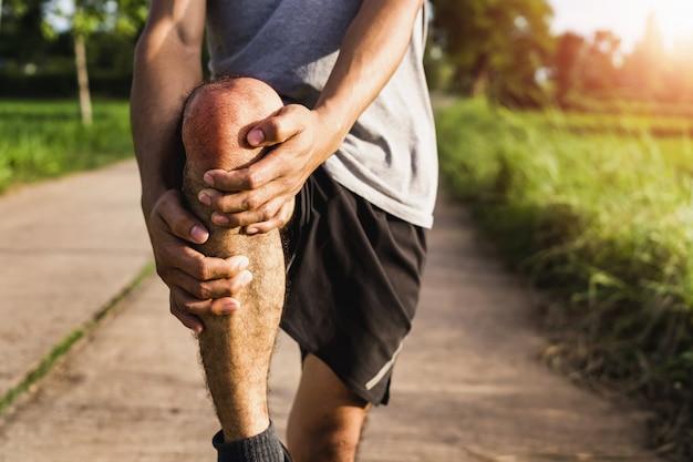 Мужчины, получившие травму от упражнений используйте свои руки, чтобы держать колени в парке Premium Фотографии