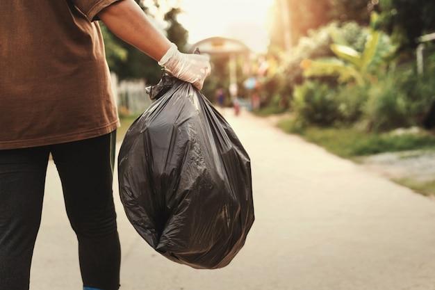 Рука женщины держа мешок для мусора для рециркуляции кладя в мусор Premium Фотографии