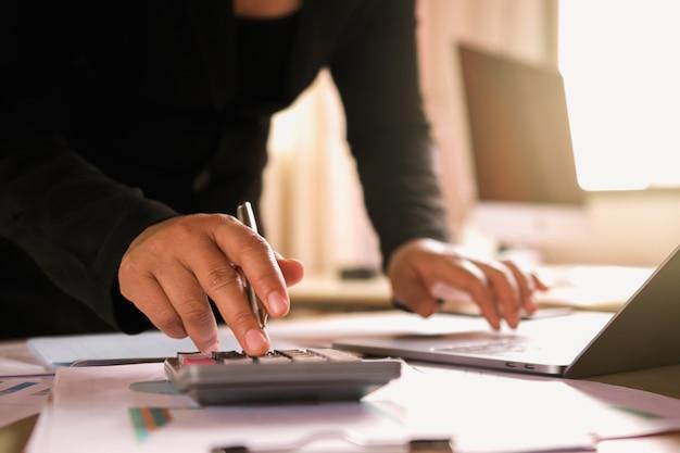 オフィスで財務のチェックデータのラップトップを使用して机の上の実業家 Premium写真
