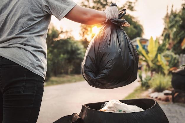 Женская рука держит мешок для мусора для очистки корзины Premium Фотографии