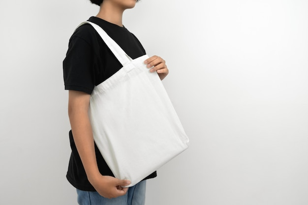 Молодая женщина, держащая эко хлопок сумка изолировать на белом Premium Фотографии