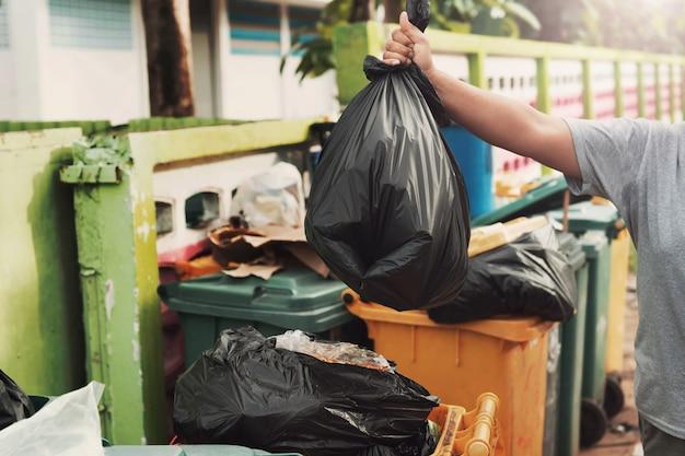 Женская рука держит мусор в черной сумке для уборки в мусор Premium Фотографии