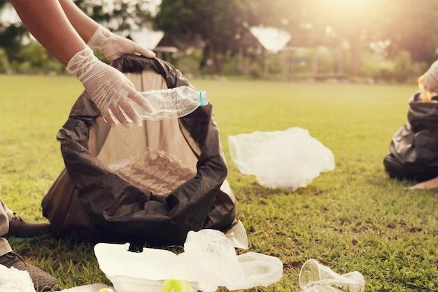 公園で清掃するためにゴミプラスチックを拾う手を閉じる Premium写真