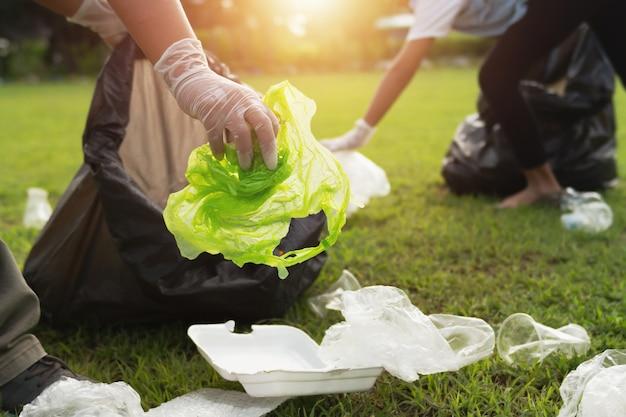 Два человека держат пластиковую бутылку для мусора в черный мешок в парке в утреннем свете Premium Фотографии