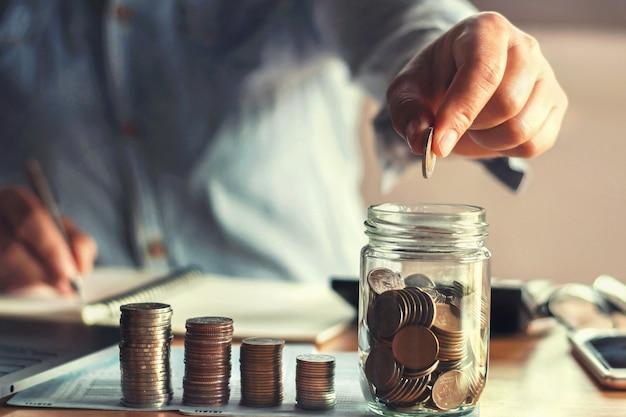 水差しガラス金融でコインを入れて手でお金を節約 Premium写真