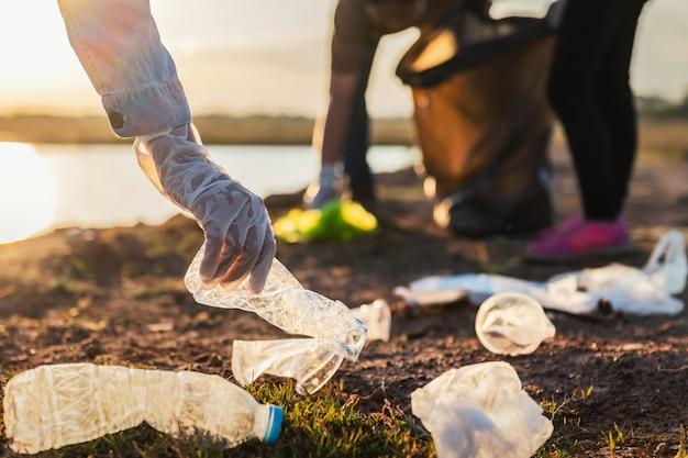 日没で公園の川でゴミ袋を黒い袋に入れてボランティアする人々 Premium写真