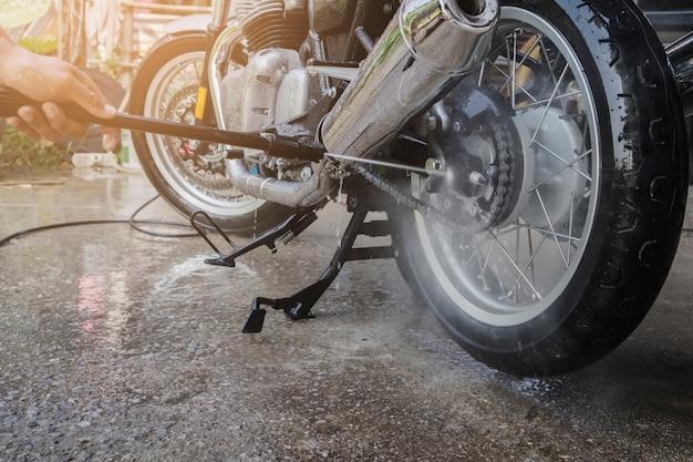 自宅でオートバイを掃除する人を洗う Premium写真